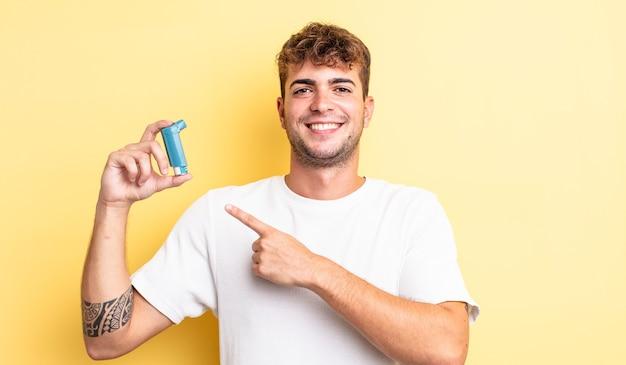 Giovane bell'uomo che sorride allegramente, si sente felice e indica il lato. concetto di asma