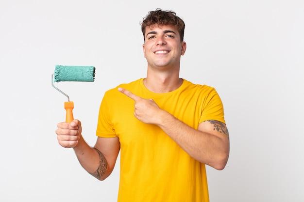 Giovane bell'uomo che sorride allegramente, si sente felice e indica il lato. dipingere il concetto di casa