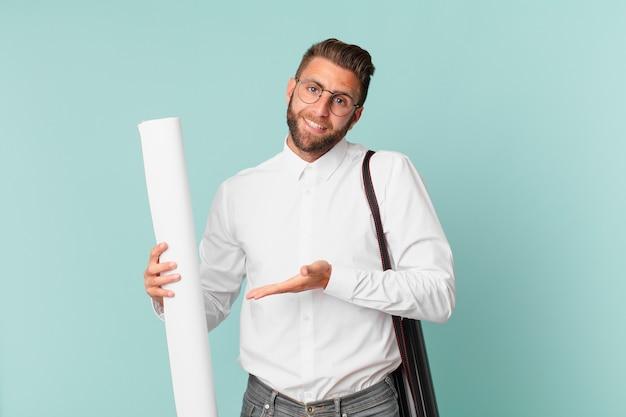 Giovane uomo bello che sorride allegramente, si sente felice e mostra un concetto. concetto di architetto