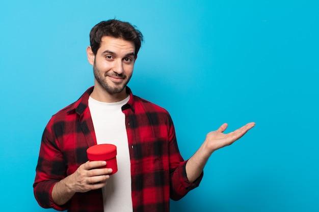 Giovane uomo bello che sorride allegramente, sentendosi felice e mostrando un concetto nello spazio della copia con il palmo della mano