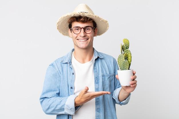 Giovane uomo bello che sorride allegramente, si sente felice e mostra un concetto. contadino con in mano un cactus decorativo