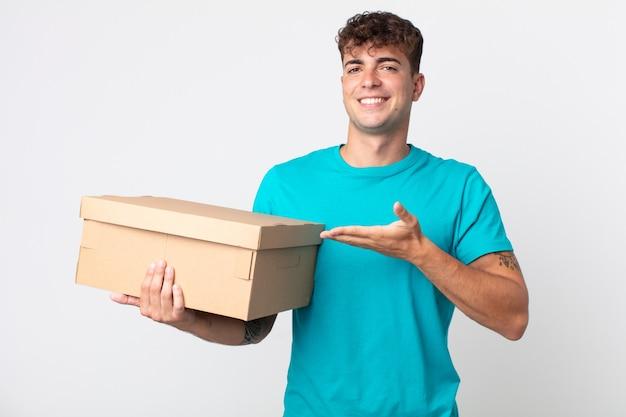 Giovane bell'uomo che sorride allegramente, si sente felice e mostra un concetto e tiene in mano una scatola di cartone