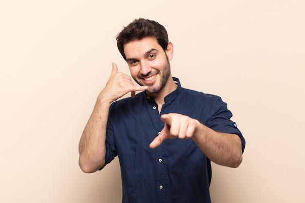 Giovane uomo bello sorridente allegramente e indicando mentre si effettua una chiamata in seguito gesto, parlando al telefono