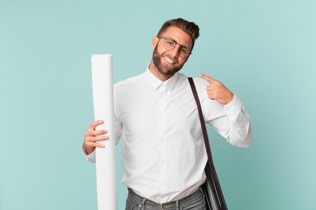Giovane uomo bello che sorride con sicurezza indicando il proprio ampio sorriso. concetto di architetto