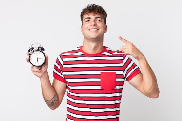 Giovane bell'uomo che sorride con sicurezza indicando il proprio ampio sorriso e tenendo in mano una sveglia