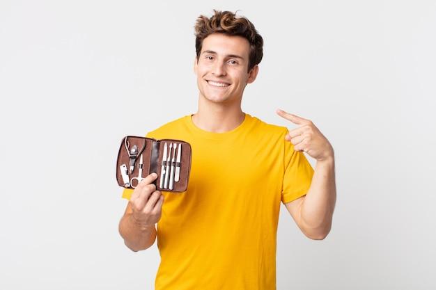 Giovane bell'uomo che sorride con sicurezza indicando il proprio ampio sorriso e tenendo in mano una custodia per attrezzi per unghie