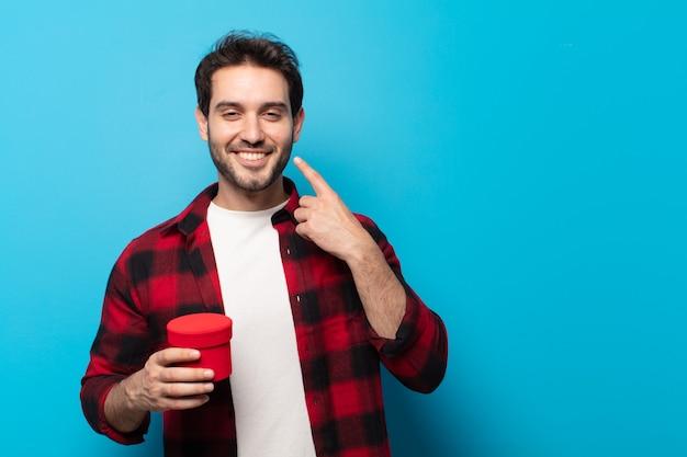 Giovane uomo bello che sorride fiduciosamente indicando il proprio ampio sorriso, atteggiamento positivo, rilassato, soddisfatto
