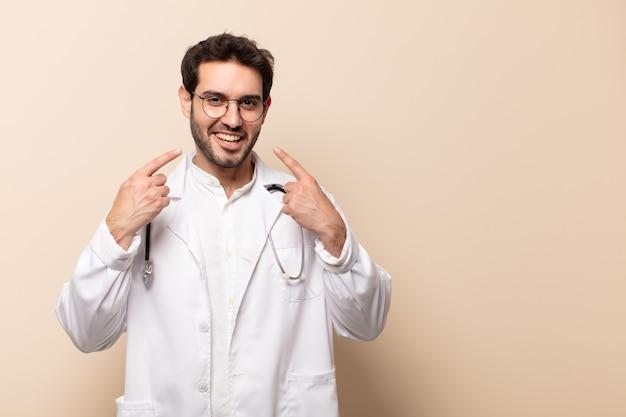 Giovane bell'uomo che sorride con sicurezza indicando il proprio ampio sorriso, atteggiamento positivo, rilassato e soddisfatto