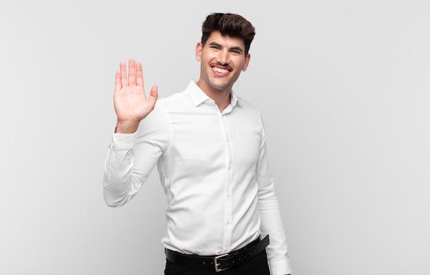 Giovane uomo bello che sorride allegramente e allegramente, agitando la mano, dandoti il benvenuto e salutandoti o salutandoti