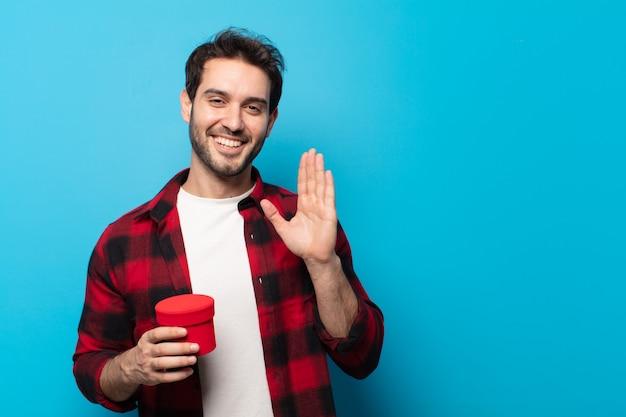 Giovane bell'uomo che sorride allegramente e allegramente, agitando la mano, accogliendoti e salutandoti, o salutandoti