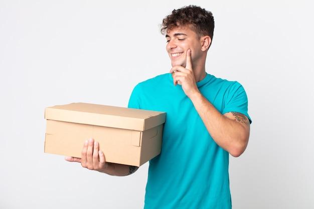 Giovane bell'uomo che sorride felice e sogna ad occhi aperti o dubita e tiene in mano una scatola di cartone