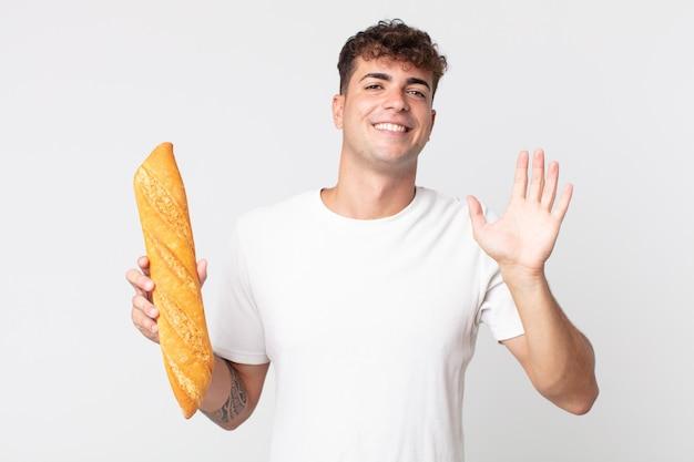 Giovane bell'uomo che sorride felicemente, agitando la mano, accogliendoti e salutandoti e tenendo in mano una baguette di pane