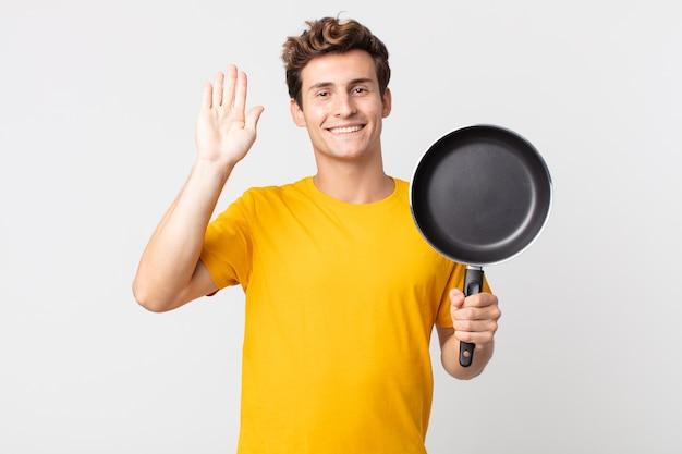 Giovane bell'uomo che sorride felicemente, agitando la mano, accogliendoti e salutandoti e tenendo in mano una padella da cucina