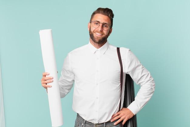 Giovane uomo bello che sorride felicemente con una mano sull'anca e fiducioso. concetto di architetto