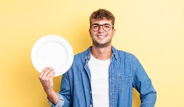 Giovane uomo bello che sorride felicemente con una mano sull'anca e fiducioso. concetto di piatto vuoto