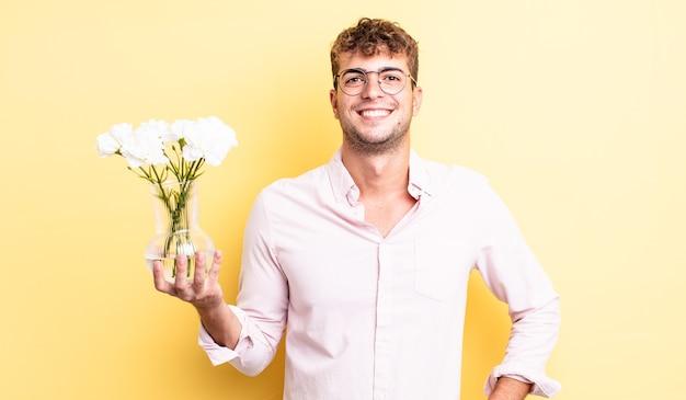 Giovane uomo bello che sorride felicemente con una mano sull'anca e fiducioso. concetto di fiori