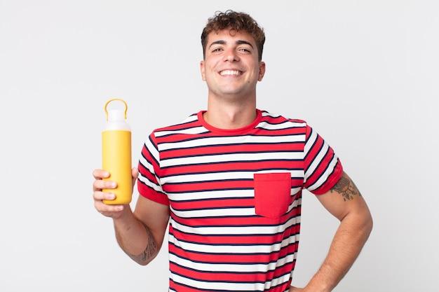 Giovane uomo bello che sorride felicemente con una mano sull'anca e fiducioso e tiene in mano un thermos di caffè