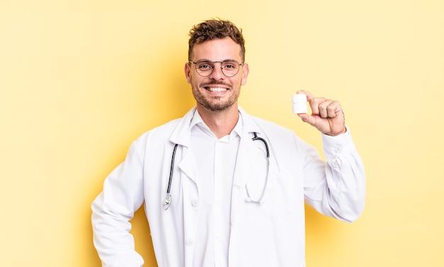 Giovane uomo bello che sorride felicemente con una mano sull'anca e fiducioso. concetto di bottiglia di pillole medico