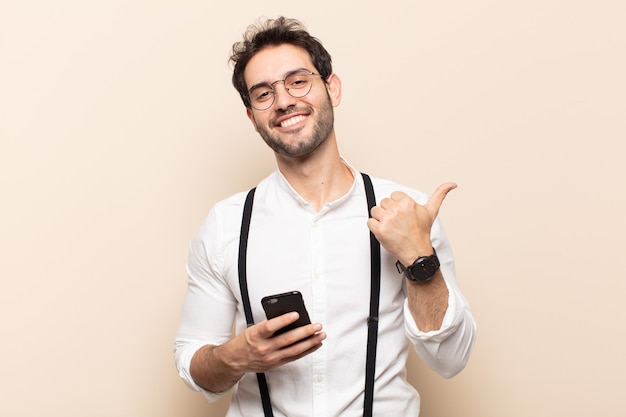 Giovane bell'uomo che sorride gioiosamente e sembra felice, si sente spensierato e positivo con entrambi i pollici in su