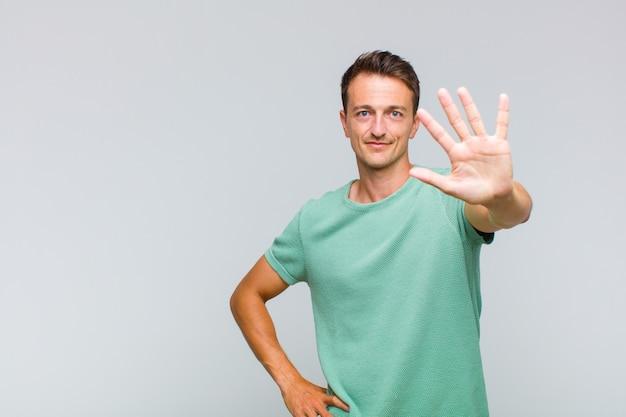 Giovane uomo bello sorridente e guardando amichevole, mostrando il numero cinque o quinto con la mano in avanti, conto alla rovescia