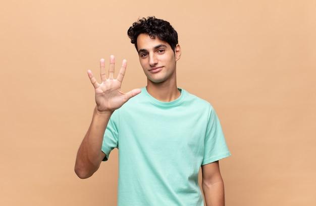 Giovane uomo bello che sorride e sembra amichevole, mostrando il numero cinque o quinto con la mano in avanti, conto alla rovescia
