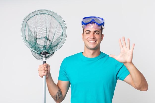 Giovane bell'uomo sorridente e dall'aspetto amichevole, mostrando il numero cinque con gli occhiali e la rete da pesca