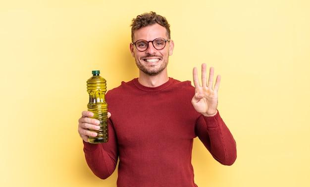Giovane uomo bello sorridente e dall'aspetto amichevole, mostrando il numero quattro. concetto di olio d'oliva