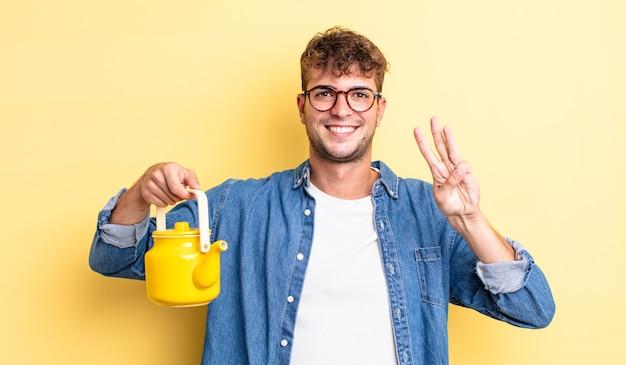 Giovane uomo bello che sorride e sembra amichevole, mostrando il numero tre.concetto della teiera