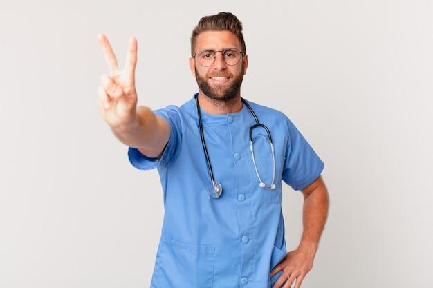 Giovane uomo bello che sorride e sembra amichevole, mostrando il numero due. concetto di infermiera
