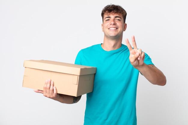 Giovane bell'uomo che sorride e sembra felice, gesticola vittoria o pace e tiene in mano una scatola di cartone