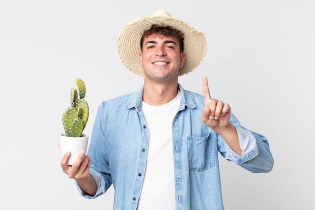 Giovane uomo bello che sorride con orgoglio e sicurezza facendo il numero uno. contadino con in mano un cactus decorativo