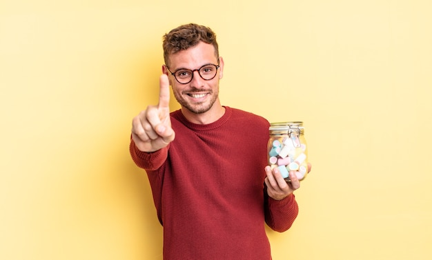 Giovane uomo bello che sorride con orgoglio e sicurezza facendo il numero uno. concetto di caramelle di gelatina