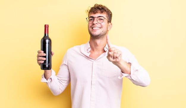 Giovane uomo bello che sorride con orgoglio e sicurezza facendo il numero uno. concetto di bottiglia di vino