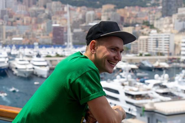Giovane uomo bello sorridente sulla nave con barche a vela offuscate e navi sullo sfondo. monte carlo, monaco.