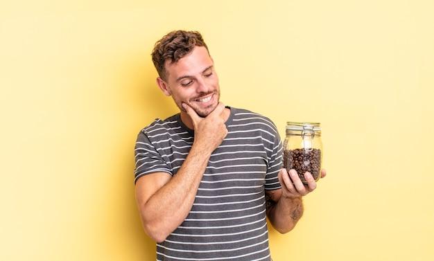 Giovane uomo bello che sorride con un'espressione felice e sicura con la mano sul concetto dei chicchi di caffè del mento