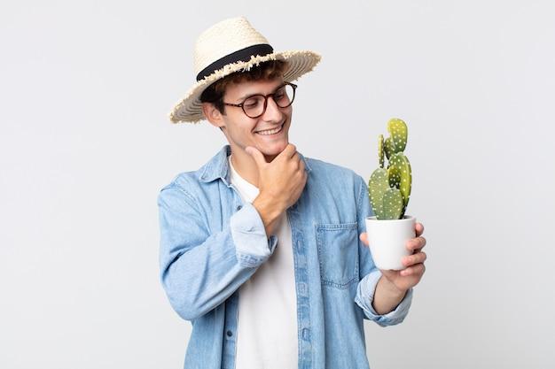 Giovane uomo bello che sorride con un'espressione felice e sicura con la mano sul mento. contadino con in mano un cactus decorativo