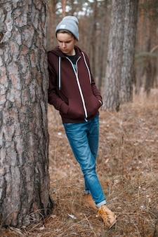 Giovane uomo bello in piedi vicino a un albero sulla foresta di autunno