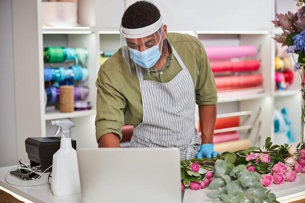 Il giovane bell'uomo con maschera sterile e vetro protettivo sta lavorando in un negozio di fiori e comunica con i clienti tramite connessione notebook