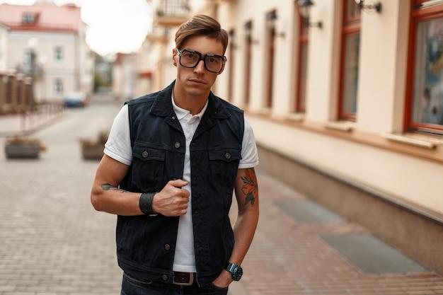 Giovane uomo bello in occhiali alla moda in gilet di jeans vintage e una camicia bianca vicino all'edificio