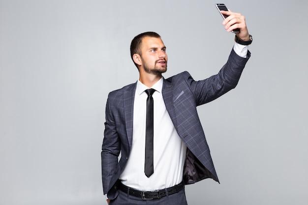 Giovane uomo bello in tuta prendendo un selfie su sfondo isolato