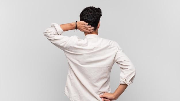 Giovane uomo bello che pensa o dubita, grattandosi la testa, sentendosi perplesso e confuso, vista posteriore o posteriore