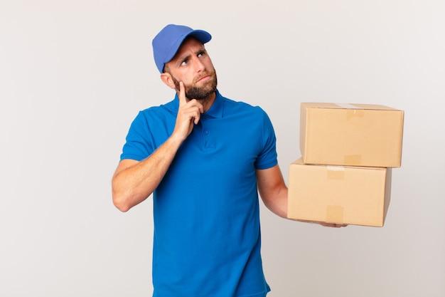 Giovane bell'uomo che pensa, si sente dubbioso e confuso. concetto di consegna del pacchetto
