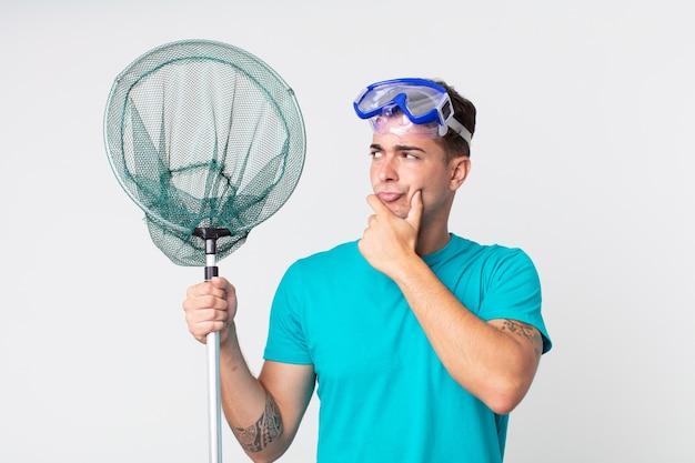 Giovane bell'uomo che pensa, si sente dubbioso e confuso con gli occhiali e la rete da pesca