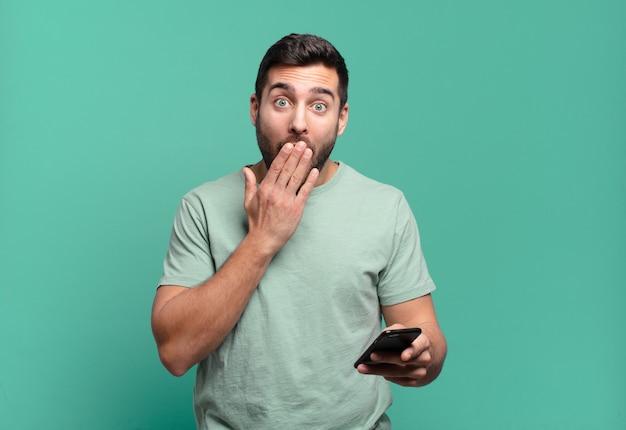 Giovane uomo bello usando il suo cellulare