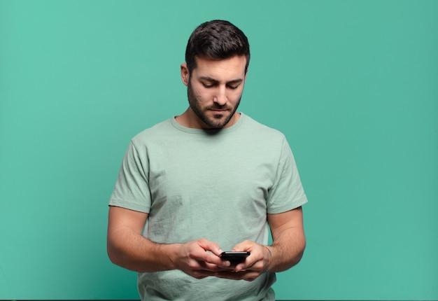 Giovane bell'uomo che usa il suo cellulare