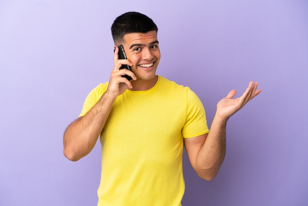 Giovane uomo bello che usa il telefono cellulare su sfondo viola isolato che estende le mani di lato per invitare a venire