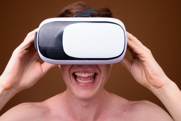 Giovane uomo bello utilizzando occhiali per realtà virtuale a torso nudo