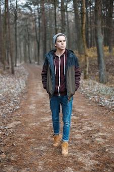 Giovane uomo bello che cammina lungo la foresta di autunno