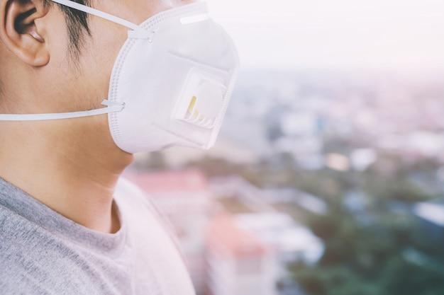 Giovane uomo bello che cammina per il mercato notturno di taipei con lo zaino e indossa una maschera antinquinamento per proteggersi dal coronavirus.