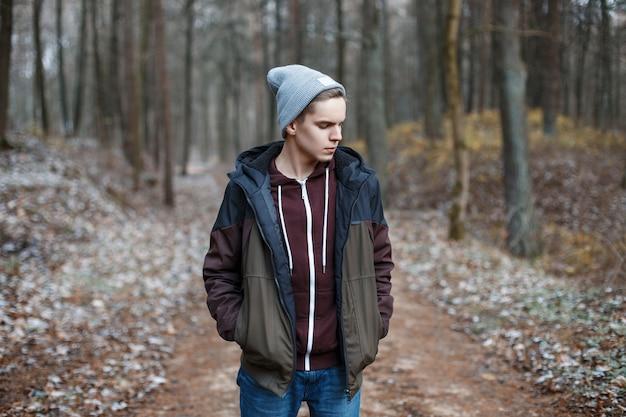 Giovane uomo bello che cammina nella foresta di autunno